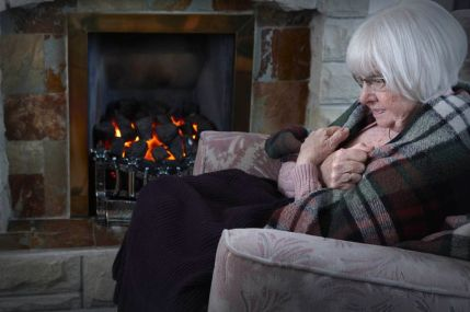 Elderly-woman-trying-to-keep-warm-by-the-fireside